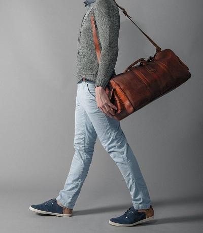 hombre modelando una bolsa de piel